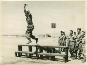 Troops practise parachute landing drills.