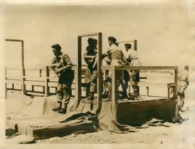 Troops practise aircraft exit drills on a wooden structure out of doors.