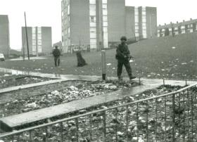 Two paratroopers on a foot patrol through a housing estate.