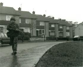 Paratrooper holding a SA 80 gun on foot patrol through a housing estate.