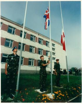 Three members of Russian Airborne Forces raise flags including the Union Flag.