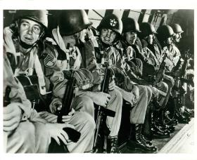 A field director (third from left) accompanies US paratroopers into battle.