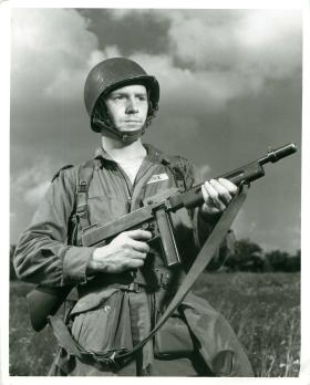 A US paratrooper stands with rifle.