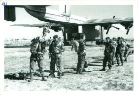 A stick of Paratroopers adjust their equipment before emplaning a Blackburn Beverley aircraft.