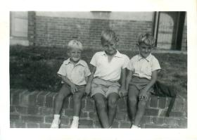 Steve Prior (right) and two of his brothers sit on a wall.