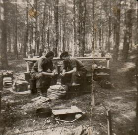 Donald Hicks peeling potatos with friend in wood
