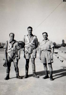 Three men prepare for parachuting, circa 1942
