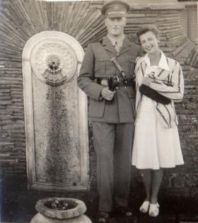 Lt Bolton and lady stand by fountain, circa 1941