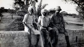 Lt Bolton sits with two locals, Jhansi, circa 1942