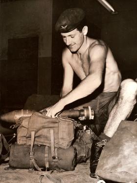 3 Para soldier preparing kit before a foot patrol, Aden, 1964
