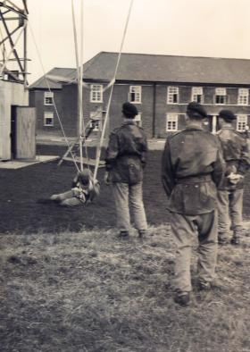 Members of 629 Airborne Light Regiment landing after jumping from the tower RAF Abingdon 1955