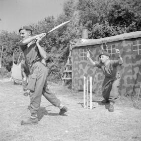 Members of 6th Airborne Divisional Signals play cricket in Normandy, 31 July 1944.