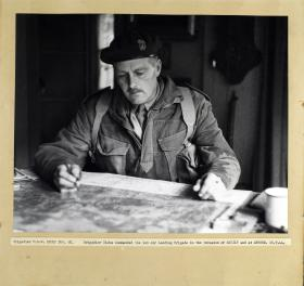Brigadier Hicks sits studying a map