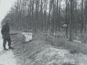 A soldier pauses by the temporary graves of the men killed at the 6km marker near Arnhem, April 1945