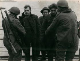 Troops search a German prisoner captured at Bruneval, 1942.