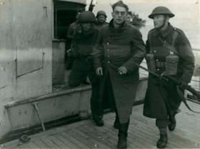 A German prisoner captured at Bruneval disembarks a landing craft.