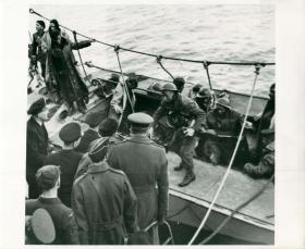 Still with blackened faces, support troops return home on landing craft.