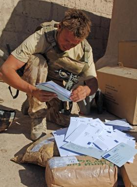 Paratrooper looking through bag of mail