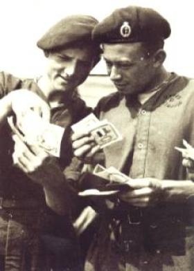 Signalmen Davis and Easby admiring the French Francs issued to them, prior to D-Day, 1944