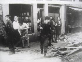 The aftermath of a bomb explosion. Paratroopers and civilians look nervously around amid debris.