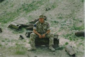 Mark Magreehan sits among spent shells, Basrah, Iraq, 2003