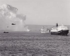 MV Norland in San Carlos Bay as HMS Antelope sinks in the background, Falklands, May 1982