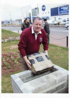 Andy Welsh MM placing a time capsule in the  Paignton Memorial