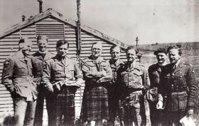 Casual group portrait of Lt Col Alistair Pearson with officers of the 8th (Midlands) Battalion, Tilshead Camp, 1944