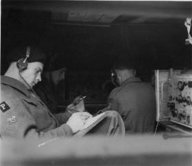 Phantom signal and coding staff at work inside a patrol scout car, mid 1940s