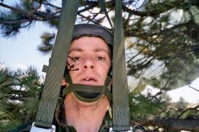 Jason Connolly hanging around after landing in a tree on exercise, Wyoming, USA