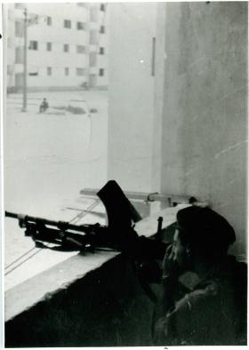 A member of the Parachute Regiment aims his gun out of a window in El Gamil.