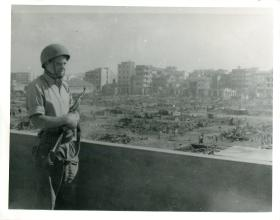 A member of 3 PARA stands on a balcony with a gun, overlooking a bomb-destroyed Port Said.