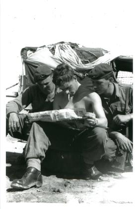 Three paratroopers crouch and read a paper in the Canal Zone.