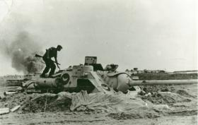 An SU-100 tank destroyer dug into sandy soil. A paratrooper stands on it holding a rifle.
