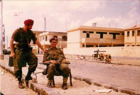A French Liaison Officer stands with a seated British paratrooper, Suez, November 1956