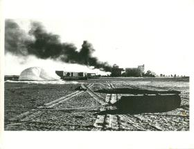 Buildings burn on El Gamil airfield. A recently dropped container can also be seen.