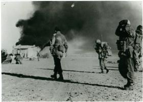 Colonel Paul Crook (left) and his tactical headquarters walk towards El Gamil airfield's control tower after dropping.