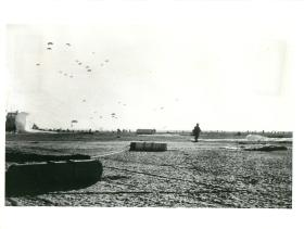Last of first lift of 3 PARA dropping on El Gamil airfield. Men are making for their RVs. November 5, 1956.