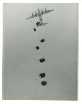 Hastings aircraft dropping arms and equipment by parachute to men on the ground.
