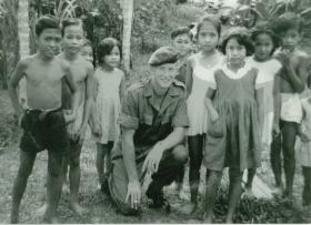 L/Cpl Denis Topping with local children in Sibu, Borneo