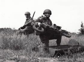 Paratrooper unloading an Airborne Welbike from supply drop container