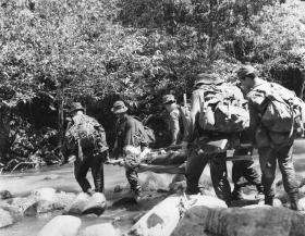 Soldiers of Guards Parachute Coy crossing a river whilst carrying a stretcher on patrol in Malaya, 1968
