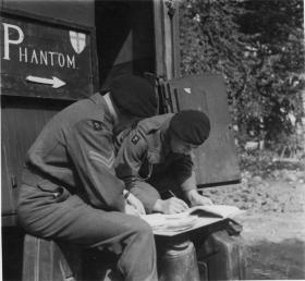 Soldiers from the Phantom GHQ Liaison Regiment draft a mission report, mid 1940s