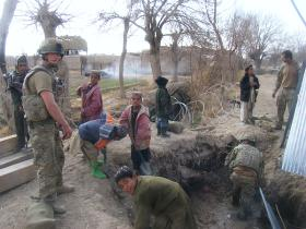 Afghan children help 9 Para Sqn Royal Engineers to excavate the site of an old bridge, Afghanistan 2011