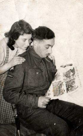 Airborne soldier reads newspaper coverage of the Bruneval raid.