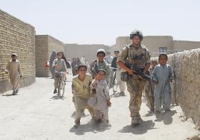 Soldier from 3 PARA on patrol alongside young Afghan locals, Kandahar, Afghanistan, 2008.