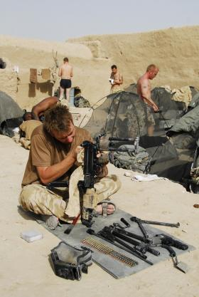 Soldier from A Coy, 3 PARA, cleaning a Light Machine Gun, Musa Qala, Afghanistan, 2008.