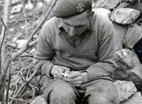 Corporal Nicks sits on a rock with a Parachute Regiment cap badge, Italy, undated.