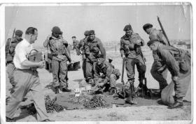 Paratroopers crowd around piles of arms and ammunition on the ground.