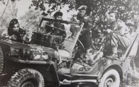Men of 2 Forward Observation Unit RA pose with their jeep